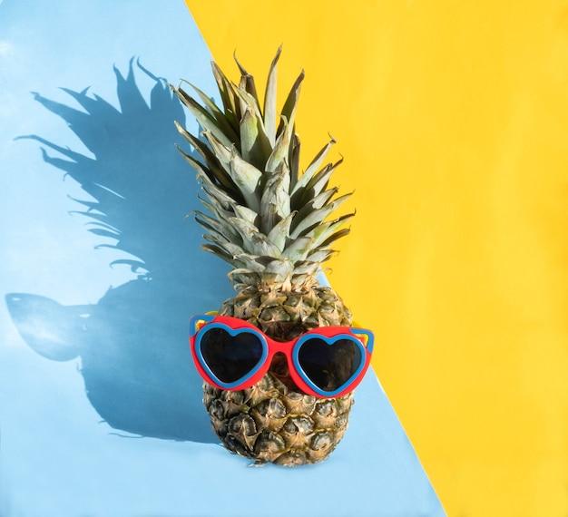 半分青と半分黄色の背景にハートのシャップサングラスのパイナップル