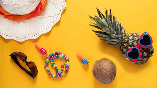 ハートのパイナップルは、黄色の背景にサングラス、麦わら帽子、その他の夏のアクセサリーを身に着けています