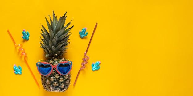 黄色の背景にプラスチック製のストローが付いたハート型サングラスのパイナップル