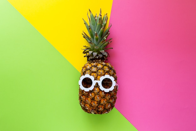 カラフルな背景、創造的な夏のコンセプトに白いサングラスのパイナップル
