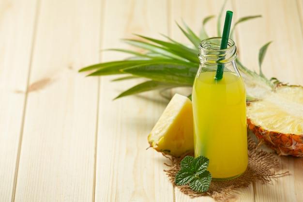Succo di ananas in bottiglia su una superficie di legno