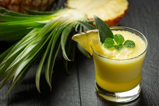 Succo di ananas su una superficie di legno scuro