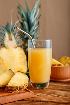 Pineapple juice in glass. glass of fresh natural pineapple juice cocktail with metal reusable tube on brown wooden table with ingredients. raw pineapple sliced fruit. high quality stock photo