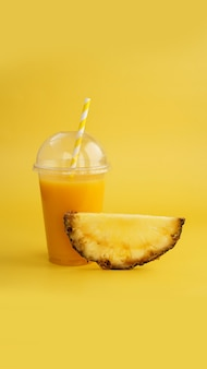 노란색 배경에 플라스틱 컵에 파인애플 주스. 열대 주스 - 여름 배너