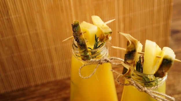 작은 병에 파인애플 주스. 파인애플 조각이 음료를 장식합니다. 나무 배경에 주스