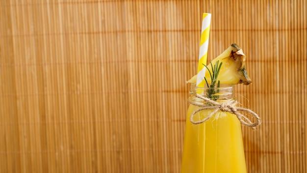 작은 병에 파인애플 주스. 파인애플 조각이 음료를 장식합니다. 나무 대나무 배경에 주스입니다. 음료에 종이 빨대