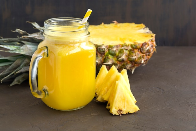 Pineapple juice in a jar with a straw