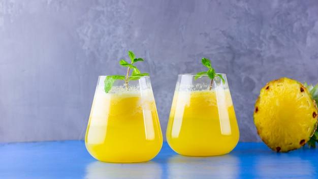 青灰色の背景にパイナップルジュース。パイナップルのスムージー。夏の飲み物