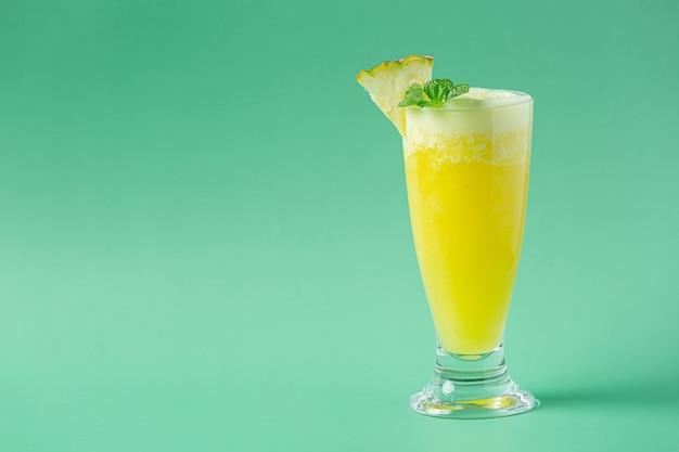 Ананасовый сок на зеленой поверхности