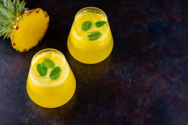 バイナップルジュース。フレッシュパイナップルのパイナップルスムージー。黒の背景に夏の飲み物