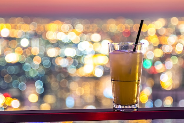 Pineapple juice in plastic glass and paper straw on the city bokeh background.
