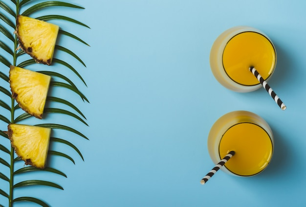Pineapple juice or smoothies and pineapple slices on a blue background