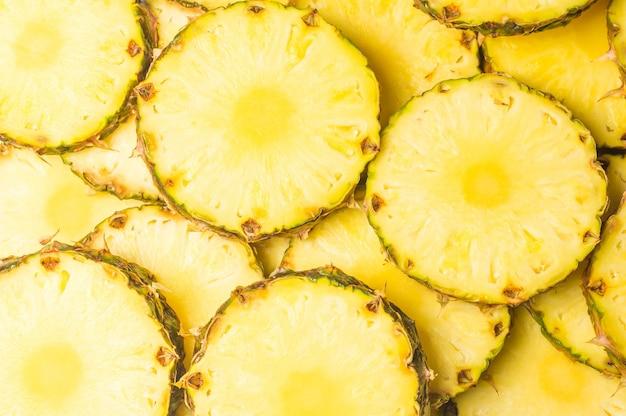 Фон сочные желтые ломтики ананаса. вид сверху.