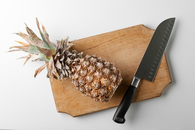 Pineapple on a kitchen board with a knife