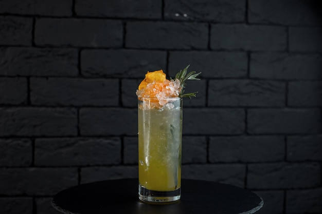 Pineapple light alcoholic cocktail in a  glass with vodka with white rum with coconut syrup with pieces of ice decorated with yellow fruit. choice of modern gourmet