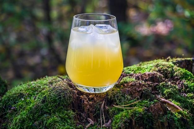 Ананас, манго, лимонный напиток в стеклянных витринах на дереве с мхом. холодный желтый коктейль с кубиками льда. живописный натюрморт с летним алкогольным напитком.
