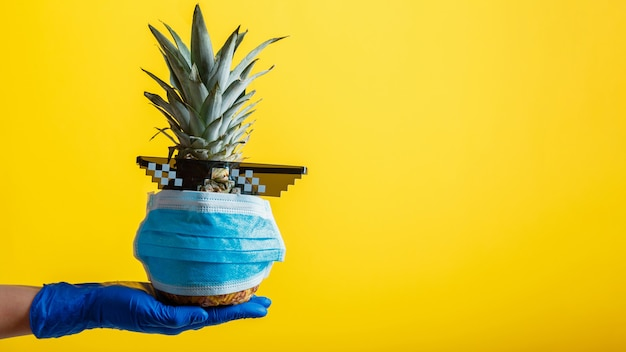 Pineapple in medical face mask and sunglasses in hand gloved on color yellow background. pineapple fruit in covid coronavirus lockdown. summer background travel and vacation concept. long web banner.