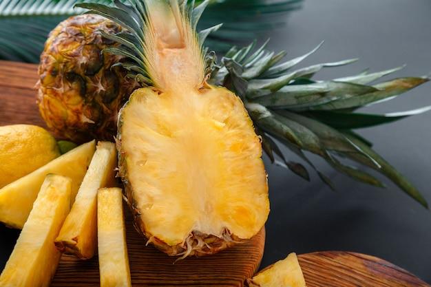 Ананас на разделочной доске. нарезанный наполовину ананас и целые плоды ананаса. летние фрукты процесс приготовления нарезанный ананас на кухне на темном фоне. фото высокого качества