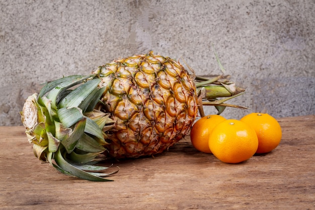 Pineapple and oranges on vintage old wooden table