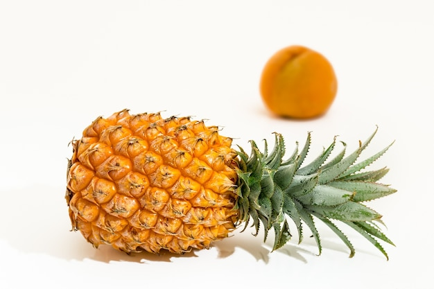 Pineapple behind a peach on a white