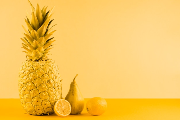 Pineapple; pear and halved lemon on yellow background