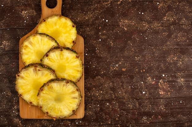 Кусочки ананаса нарезанные свежие спелые сочные вид сверху на коричневый деревянный стол и деревенский фон