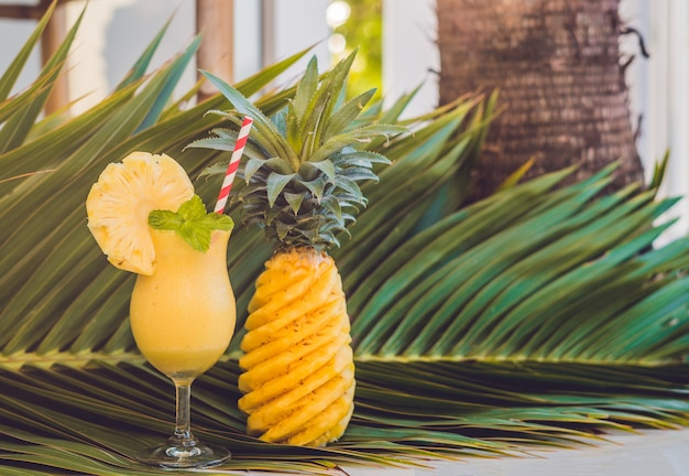 Pineapple and pineapple smoothies against the surface of a branch of a palm tree