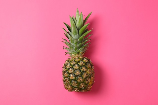 Pineapple on pink background, space for text. juicy fruit