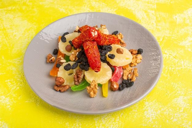 Anelli di ananas insieme a frutta secca e torrone all'interno del piatto su giallo