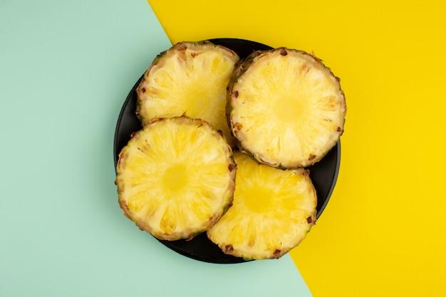 Кольца ананаса свежие сочные спелые внутри черной пластины вид сверху на красочный стол