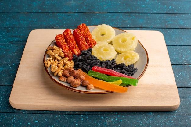 Anelli di ananas con frutta secca, noci e gelatine sul blu