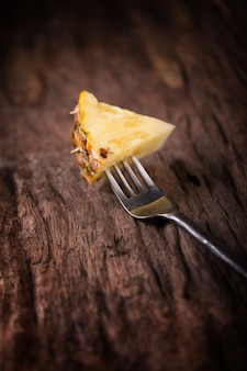 Pineapple slices and pineapple shelled asian-style on the old wooden background