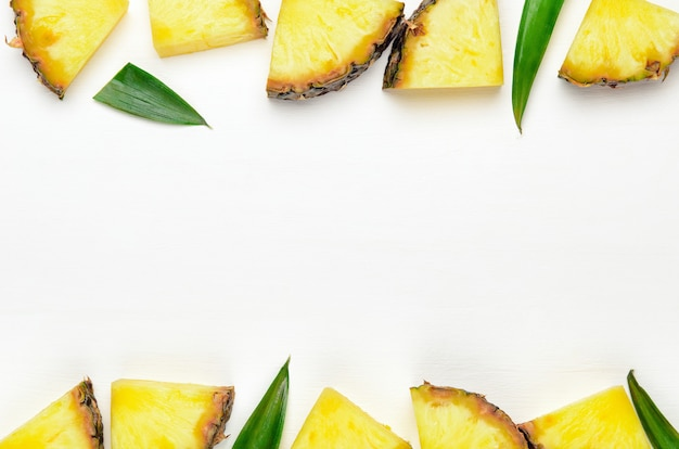 Pineapple slices with green leaves of pineapple on a white wooden background frame.