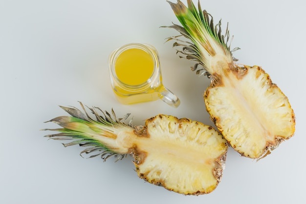 Pineapple slices with juice on white surface