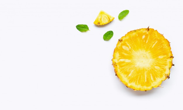 Pineapple slices with mint leaves on white background.