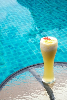 Pineapple  smoothie in tall glass with swimming pool background.