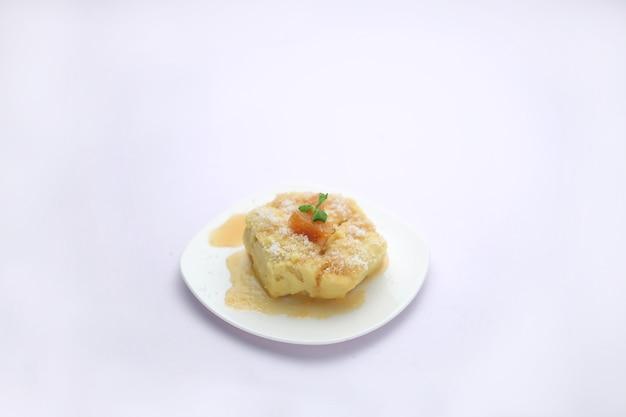 파인애플 수플레, 달콤한 수플레는 흰색 질감의 흰색 원형 접시에 소스와 함께 제공됩니다.