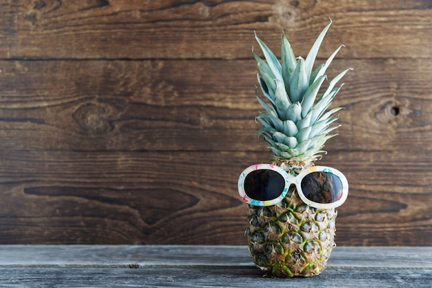 Pineapple in sunglasses in the background