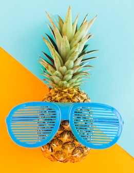 Pineapple in sunglasses on colorful background