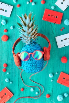 Pineapple in sunglasses and earphones on turquoise wood with audio tapes