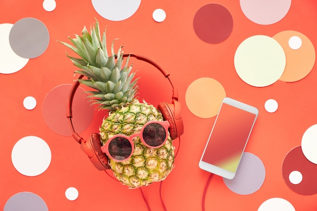 Pineapple in sunglasses and earphones with smart phone on turquoise wooden board