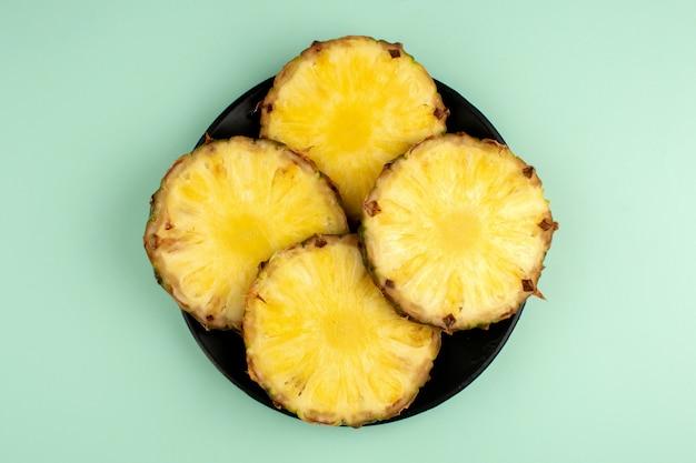 Ananas una vista dall'alto di fresco affettato maturo fresco all'interno della banda nera e su un blu