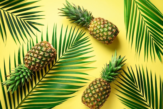 Pineapple and tropical palm leaves on yellow background. summer concept.
