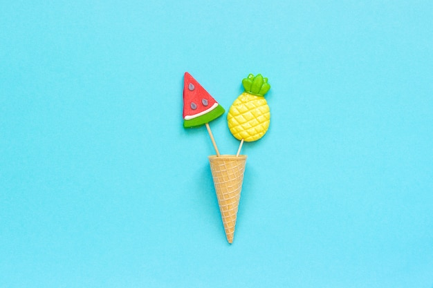 Pineapple and watermelon lollipops in ice cream cone on blue
