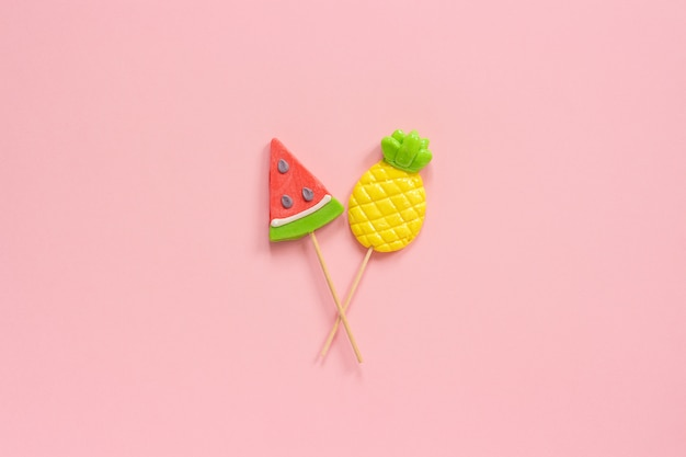 Pineapple and watermelon lollipops on stick on pink background. concept summer vacation or holidays