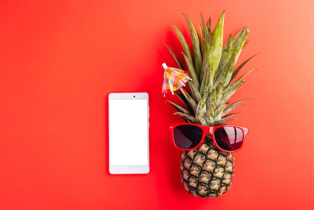 Pineapple wear red sunglasses and smartphone blank screen, flat lay