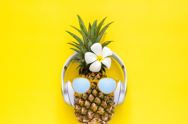 黄色の背景に白いフランジパニの花とサングラスとワイヤレスヘッドフォンを身に着けているパイナップル。最小限の夏のコンセプト。