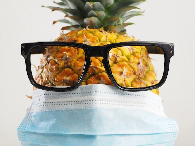 Pineapple wearing surgical mask and glasses on white background. protection from coronavirus covid-19.