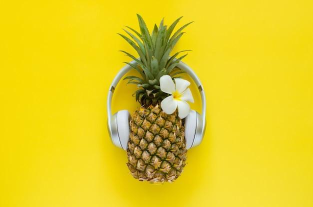 黄色の背景に白いフランジパニの花とワイヤレスヘッドフォンを身に着けているパイナップル