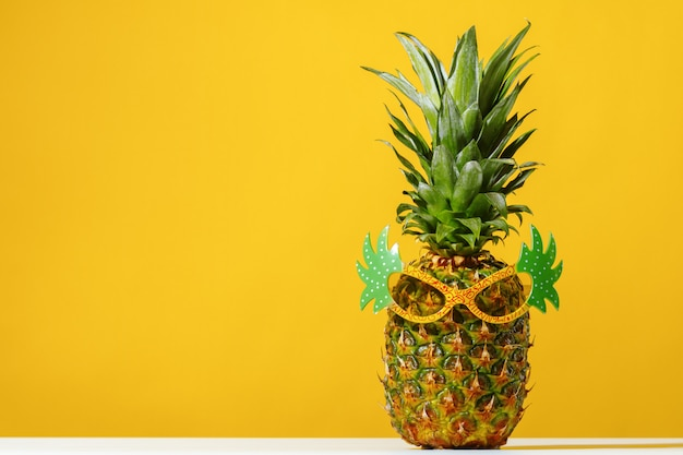 Pineapple wears sunglasses on background
